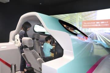 鉄道博物館の新館でE5系の運転シミュレーターを体験する来館者=5日午前、さいたま市