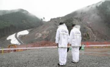 砂崩れの現場で黙とうする警察官=5日正午、日田市小野地区