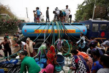 インド・ニューデリーで、給水車から容器に飲料水を入れる住民たち=6月26日(ロイター=共同)