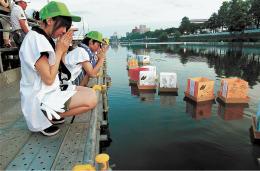 灯籠に手を合わせる子どもたち。資金不足で開催継続が危ぶまれている=2016年8月20日、仙台市若林区(実行委提供)