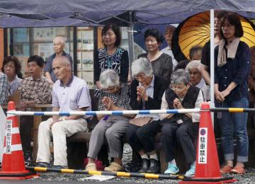 九州北部豪雨から1年を迎え、福岡県朝倉市の仮設住宅で行われた追悼式で手を合わせる住民ら=5日夕