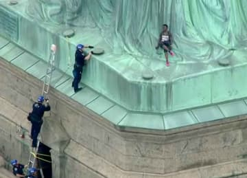 Woman climbs Statue of Liberty as Trump immigration policy protest