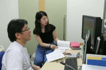 母子手帳や日本小児科学会の関連ホームページを見ながら相談に対応する是松聖悟副院長(左)=中津市民病院