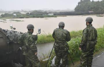 大雨の影響で増水した桂川に架かる久我橋付近で活動する自衛隊員=6日午前6時34分、京都市