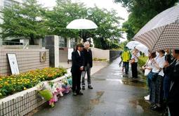 校門の前で教育への思いを語る参加者ら=6日午前、神戸市西区美賀多台9(市民グループ「生命の管理はもうやめて!」提供)