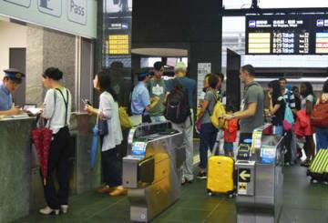 駅窓口に並んだり、スタッフに運行状況を尋ねたりする観光客たち(京都市下京区・JR京都駅)