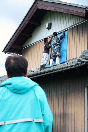 雨がやんだ合間に、外壁にブルーシートをくぎで打ち付ける作業を見守る住民(5日午後3時2分、米原市朝日)