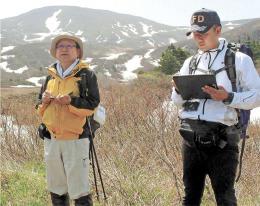栗駒山山腹で噴気の温度を調べる土井さん(左)