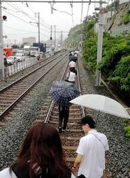 山陽電鉄須磨浦公園-塩屋間で線路上に土砂が流れ込み、立ち往生した電車を降りて線路を歩く乗客ら=6日午後3時29分、神戸市垂水区塩屋町