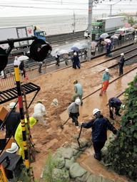 土砂の撤去作業を急ぐ作業員ら=6日午後、神戸市垂水区(撮影・大山伸一郎)