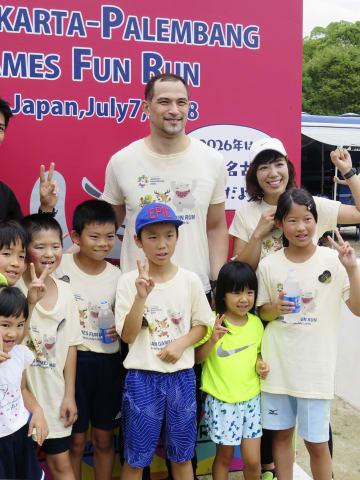「ファンラン」イベントで、参加者と写真撮影に応じる室伏広治さん(中央)=7日、名古屋市の名城公園