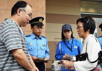 チラシを手渡し、情報提供を呼び掛ける横山さん(左)と須永署長(左から2人目)=イオンモール太田