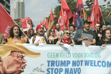 7日、ブリュッセル中心部で、トランプ米大統領の訪問に反対しデモ行進する人々(共同)