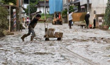 泥で埋め尽くされた道路を台車でごみ運びする男児(8日午前10時11分、京都府福知山市大江町)