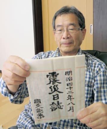 「震災日誌」を手にする小林さん(長浜市国友町)