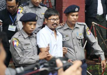 起訴され、裁判所を後にするロイター通信の記者(中央)=9日、ミャンマー・ヤンゴン(共同)