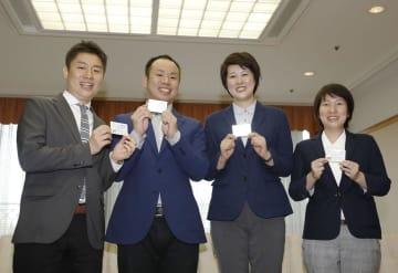 「パートナーシップ宣誓証明制度」の受領証を手に笑顔を見せるカップル=9日午後、大阪市役所