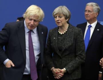 英国のメイ首相(中央)と話すジョンソン氏(左)=5月、ブリュッセル(AP=共同)
