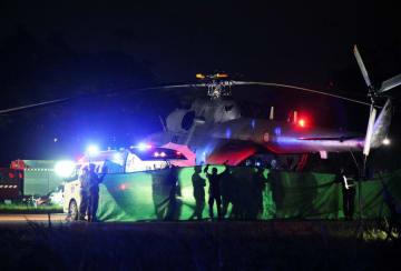 9日、タイ北部チェンライ県で、軍のヘリコプターから待機する救急車に運ばれる少年ら(ロイター=共同)