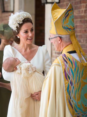 9日、ロンドンのセントジェームズ宮殿の礼拝堂で、ルイ王子を抱くキャサリン妃(左)(ロイター=共同)