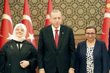 9日、トルコ・アンカラの大統領府で、新内閣の2人の女性閣僚に挟まれるエルドアン大統領(中央)(共同)