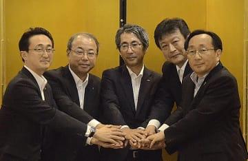 協定調印後に握手する小早川智明社長(右から2人目)、川崎敏寛社長(中央)ら=9日、青森市