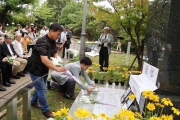 追悼碑に献花する王金華さん(手前左)と王洪傑さん(手前右)=長崎県長崎市、平和公園