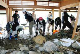 屋内に残った大量の泥や岩をかき出すボランティア=10日午前9時55分、宍粟市一宮町