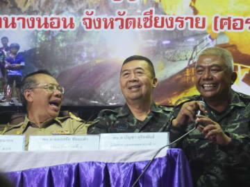 9日、タイ北部チェンライ県で、4人の救出後に記者会見し、笑顔を見せる当局者(共同)