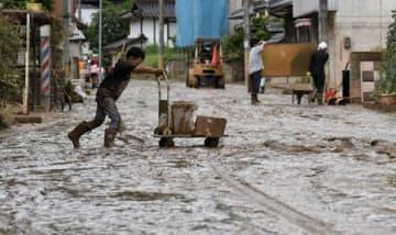 泥で埋め尽くされた道路を台車でごみ運びする男児(8日午前10時11分、福知山市大江町蓼原)