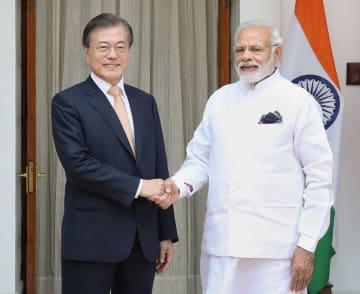 10日、インド・ニューデリーで開かれた首脳会談で握手する韓国の文在寅大統領(左)とモディ首相(聯合=共同)