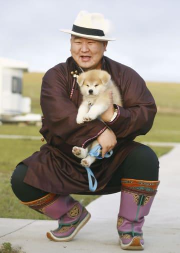贈呈された秋田犬「マサオ」を抱く大相撲の元横綱朝青龍、ドルゴルスレン・ダグワドルジ氏=10日、ウランバートル近郊(共同)