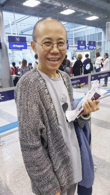 北京から経由地のヘルシンキに到着し、笑顔で写真に納まる劉霞さん=10日(提供写真・共同)