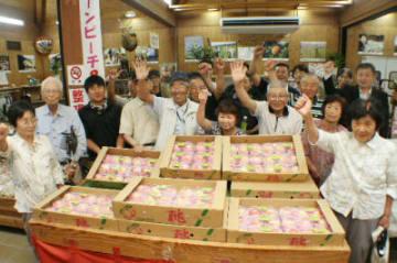 旬を迎えたクリーンピーチを囲む生産者=10日、豊後大野市清川町