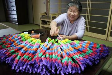 1年間で1万4000羽の折り鶴を制作した藤原さん。針と糸を使って1000羽ずつ束にしている=長崎県五島市玉之浦町