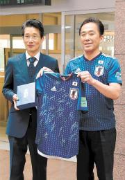 福島県広野町に寄贈した日本代表のサイン入りユニホームを遠藤町長(右)に手渡す西さん