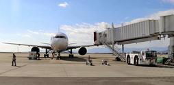 航空機のドアの10センチ手前まで自動で近づく旅客搭乗橋(右)=徳島県松茂町、徳島阿波おどり空港(新明和工業提供)