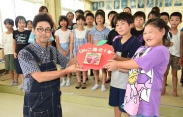 「りんご畑の1年」のDVDを八重畑小の児童に贈呈する宇津宮邦昭会長(手前左)