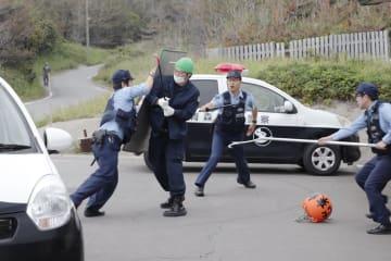 不審船の乗員が上陸した想定訓練で、抵抗する男を取り押さえる警察官=12日午前、青森県つがる市
