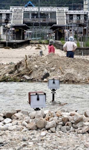 土石流が流れ込み、線路が土砂で覆われたJR山陽線瀬野駅付近。踏切があった場所には川のような流れもできている(11日午後3時17分、広島市安芸区)