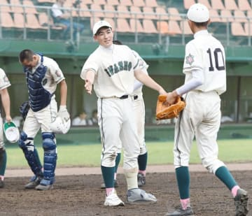 試合中、岩槻商のエース長嶋豪投手(中央)がベンチ前で先発した1年生の大槻駿也投手(右)を出迎える=12日午前、市営大宮球場