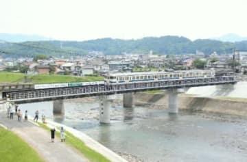 住民らが見守る中、新しい花月川橋梁を通過する試運転の列車=12日、日田市渡里