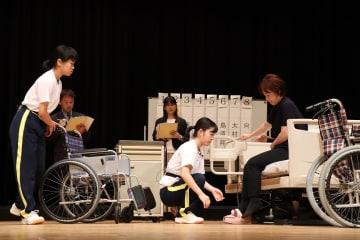 2人一組で高齢者役をベットから車いすに移動させる高校生=シーハットおおむら