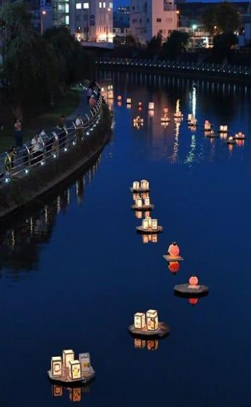 平和への願いを込めて流された灯ろう=12日午後7時25分、宇都宮市大通り4丁目の田川