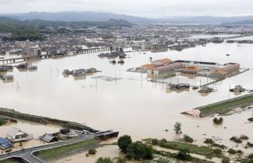 水に漬かった岡山県倉敷市真備町地区。手前は決壊した堤防=8日