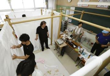 避難所の小学校に設置された、紙筒と布を組み合わせた間仕切り。中央奥は被災者(右の2人)と笑顔を見せる建築家の坂茂さん=13日午後5時55分、岡山県倉敷市真備町地区