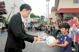 サッカーボールにサインする柴崎選手(左)