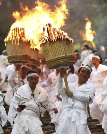 「那智の扇祭り」で、燃えさかる大たいまつを担いで参道を練り歩く白装束の氏子たち=14日午後、和歌山県那智勝浦町の熊野那智大社