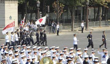 フランス革命記念日の軍事パレードで日の丸を掲げて行進する自衛隊員ら=14日、パリ(共同)