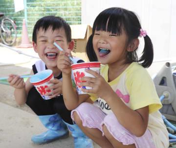 無料で振る舞われたかき氷に笑顔の坂本結香ちゃん(右)ら=14日、岡山県倉敷市の真備町地区
